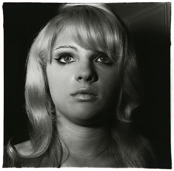 Diane Arbus (1923 - 1971) 	BLONDE GIRL WITH SHINY LIPSTICK, N.Y.C. 1967 	Gelatin silver print 	14 7/8 x 15 1/8 inches 	37.8 x 38.4 centimeters